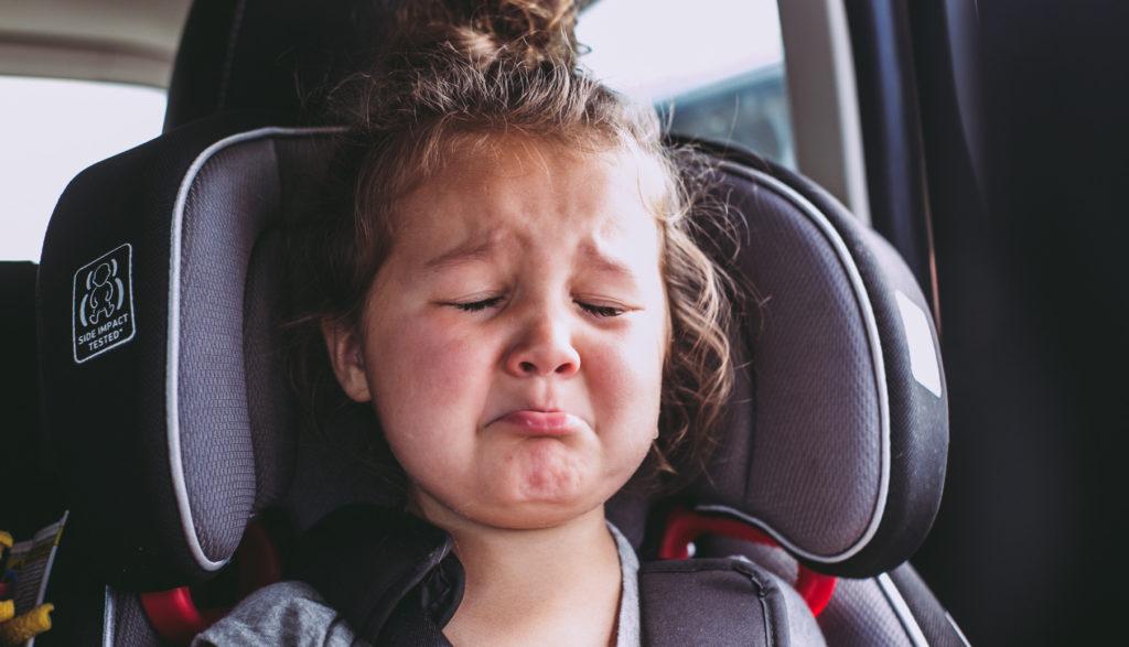 Girl bored in car seat