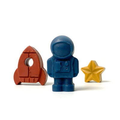image shows three space shaped crayons, red rocket, blue astronaut and yellow star