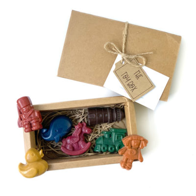 image shows a cardboard box with 7 toy shaped crayons inside